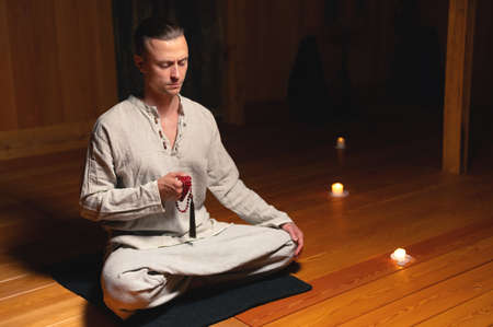 A portrait of an attractive Caucasian man sits in cotton robes in a lotus pose in a dark wooden practice room surrounded by candles