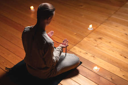 A man in clothes for practice and meditation sits in a lotus pose and holds red rosary to concentrate attention in a wooden room with dim light back view