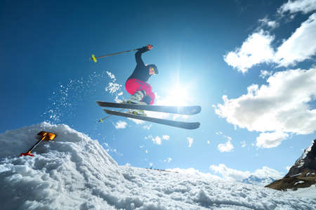 A young woman in sunglasses in tension jumps on skis from a springboard of snow against the blue sky and clouds. Uncertain performance of a trick on skis Standard-Bild