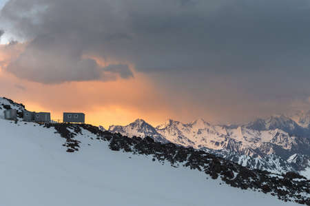 The southern slope of Mount Elbrus. Homemade shelters on the slope for the summit day at sunset against the backdrop of the main Caucasian ridge Stok Fotoğraf