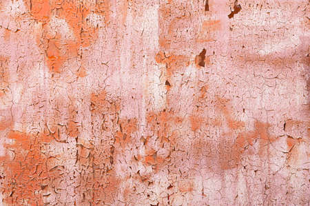 Textured background old faded red paint with white streaks and cracked peeling to rusty metal