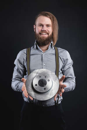 A bearded stylish man in the wheelhouse with suspenders smiles, looking at the camera, and holds a car brake disc in his hand. Ideal auto parts seller Banque d'images - 157812445