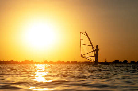 A beginner windsurfer woman stands on a board with a sail on a sunset background. Windsurfing school