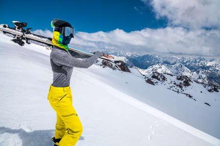 Close-up young woman skier in a ski mask with a closed face holds skis on her shoulder against the backdrop of snow-capped mountains