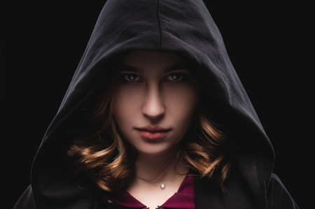 Close-up portrait of a secretive young girl in a deep dark hood on a black background. The concept of secrecy of secrets and people hiding from the government.
