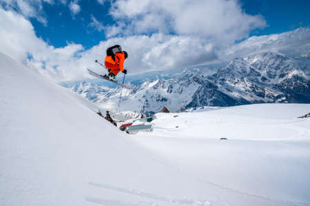 Professional athlete skier freerider in an orange suit with a backpack flies in the air after jumping on the lags on the background of blue snow and mountains Stock Photo