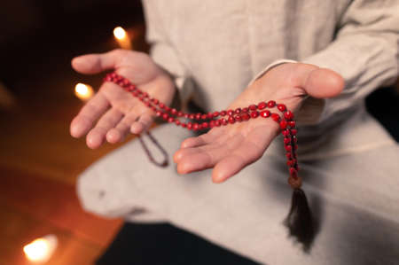 close-up the male hand of a monk practicing meditation holds a red rosary in a dark room by candlelight. Practice and enlightenment Stockfoto