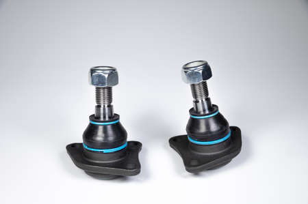 Two ball joint car suspension on a gray background. New spare parts axel car elements