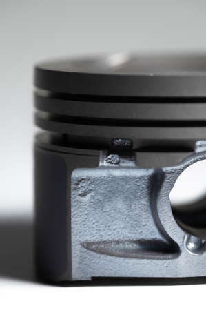 Close-up piston of an internal combustion engine on a gray background. New spare parts for engine repair. Repair background