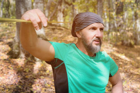 Portrait of a bearded man in age stands near a taut slackline in an autumn forest