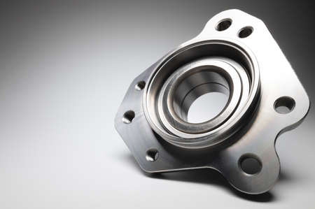 New wheel bearing in a metal housing on a black-white gradient background. New car suspension parts