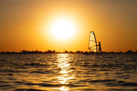 Silhouette woman windsurfer on waves of the bay at beautiful sunset