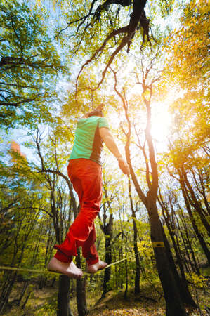 An adult bearded man balancing on a tight slackline is engaged in balancing act in the autumn forest