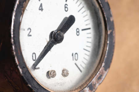 Close-up of an old industrial pressure gauge display with worn protective glass. Macro