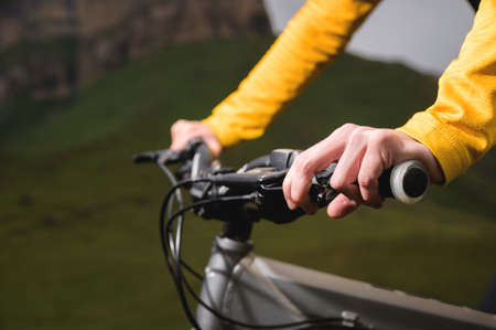 Close-up of female hands holding the handlebars of a mountain bike in the summer in the mountains
