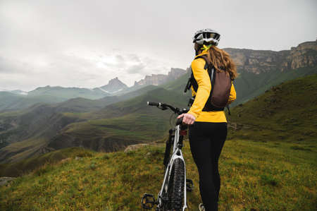Wide angle bottom view of a young woman sitting on a mountain bike high in the mountains against the backdrop of epic rocks in the evening. Mountain sports bike