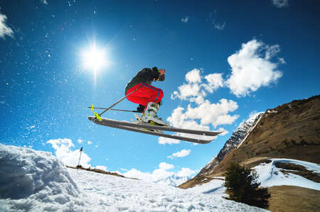Young sportswoman woman jumping from a snow springboard high in the mountains Foto de archivo