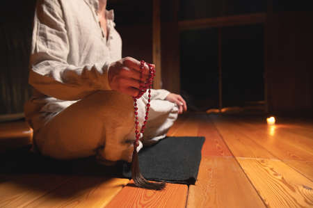 Close up of mens hands with rosary. Young man doing yoga indoors on a black rug. spirituality and practice religion concept