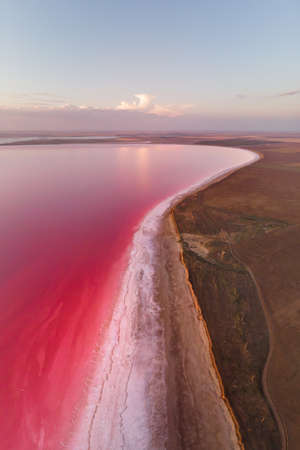 Vertical panoramic salty lake shore with pink salt at dusk after sunset. Aerial view Stock fotó