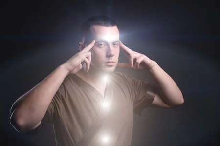Portrait of an enlightened Caucasian male physiotherapist with glowing chakras. The telepath holds his fingers to the scales while reading your mind