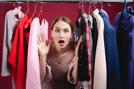 Surprised young woman in stupor and confusion chooses between different clothes with a sad face Stock Photo