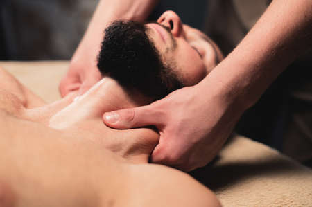Close-up Professional neck massage to a bearded male athlete in a dark room of a spa massage room