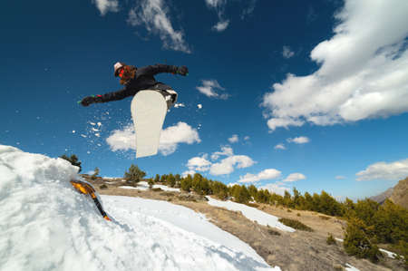 Snowboarder woman jumping from a kicker springboard from the snow on a sunny day in the mountains in a homemade snowboard park Imagens