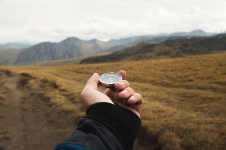 First-person view of a male traveler s hand holding a magnetic compass against the backdrop of a mountainous area. Orientation and finding your way Banque d'images