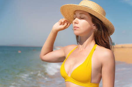 Portrait of a happy young Caucasian woman in a yellow swimsuit and a straw hat is standing in the water with her eyes closed with pleasure and enjoying sunbathing. 版權商用圖片