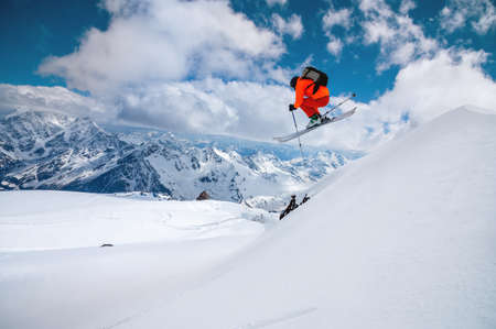 A freerider skier in an orange suit with a backpack froze in a jump flight over high snow-capped peaks in the mountains on a sunny day Banque d'images