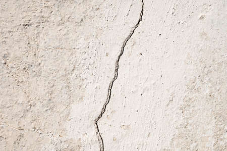 Grunge gray background of cracked peeling walls with peeled putty in beige tones.