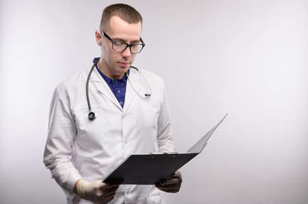 Portrait of an attractive young Caucasian doctor in glasses and a white coat stands with a tablet in his hands smiling and looking at tablet on a gray background. Studio portrait copy space