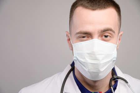 Portrait of a young friendly friendly Caucasian doctor in a protective medical mask on a gray background. A man winks and smiles with his eyes looking at the camera