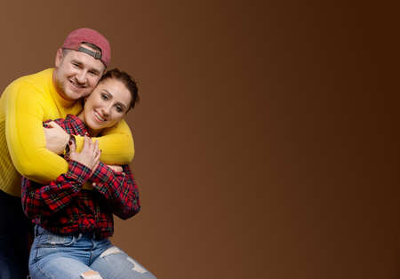 Caucasian married couple man and woman hugging and kissing with closed eyes. The casual style and flamboyant attire of a typical studio portrait of a 30-year-old couple. Copy space for your text Stock fotó