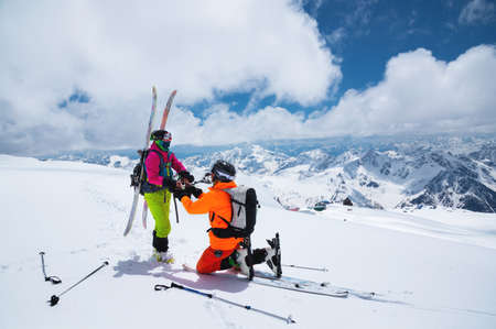 A young male skier stands on his knee inviting his beloved girlfriend, a skier, to become his wife high in the mountains against the backdrop of snow-capped peaks on a sunny day