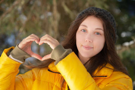 Attractive young Caucasian woman in a down jacket and hat shows a gesture of heart and love to the camera with her hands. Against the background of a coniferous winter forest