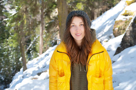portrait of an attractive caucasian young woman in a knitted hat and yellow jacket standing in the forest and looking at the camera smiling against the background of a winter coniferous forest