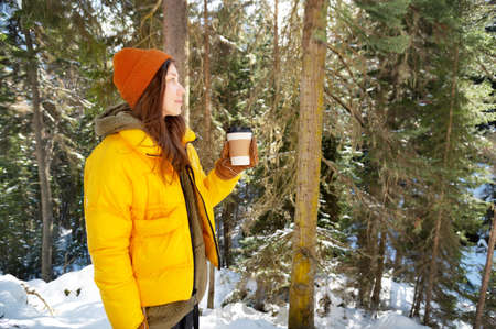 Young attractive caucasian woman in a hat and yellow down jacket stands in a winter forest on a sunny day with a paper cup of coffee in her hand