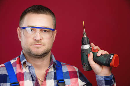 caucasian worker in glasses with a screwdriver in his hands stands in the studio Stock fotó