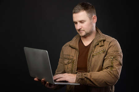 A portrait of a focused Caucasian man with a laptop in his hands stands in the studio and looks attentively into the laptop. The concept of using pc and mobile remote access to services
