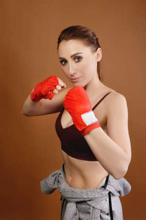 A studio portrait of an attractive Caucasian young woman fighter with bandages on her fists preparing for a fight and looking at the camera. Combat fitness concept. Fitness club advertising Stock fotó