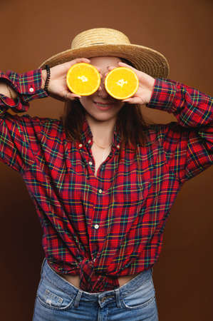 smiling woman hold halves of an orange in her hands instead of eyes. straw hat, plaid shirt, studio shooting