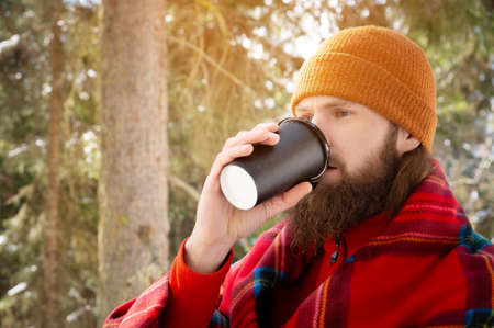 bearded man drinking from a paper cup with a blanket on his shoulders Stock fotó