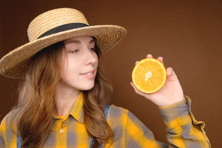 A young attractive Caucasian woman with long hair in denim overalls and a straw hat holds a cut orange in her hands and looks at the fruit. Freshness of orange flavor and summer on brown background