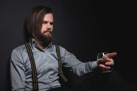 Man with beard holds glass brandy. Bearded drink cognac. Sommelier tastes drink. Man holding a glass of whisky. Sipping whiskey.