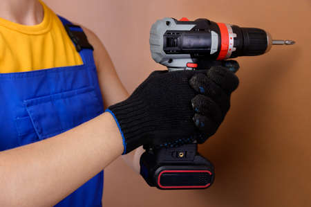 Female hands of a foreman in work gloves holds an electric screwdriver. Studio photography on a brown background Foto de archivo