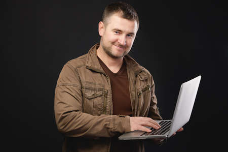 A portrait of a focused happy smile Caucasian man with a laptop in his hands stands in the studio and looks at camera. The concept of using pc and mobile remote access to services