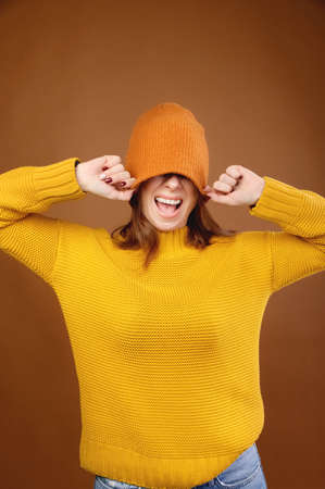 A portrait of a cheerful happy girl with light brown long hair having fun, covering her eyes with a large knitted noose hat, smiling broadly with perfect white teeth in a yellow sweater