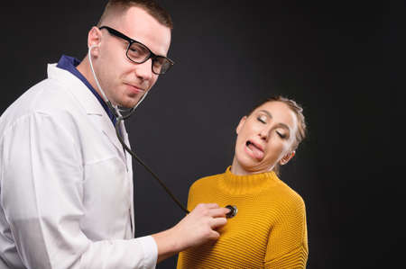A young doctor with glasses listens to the heartbeat of a woman making faces. Medical humor. False diseases