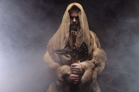 Copy space portrait mysterious man in robes and furs stands and holds an ancient ax in his hands, a dark room with smoke Foto de archivo